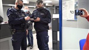 Na zdjęciu umundurowani policjanci podczas legitymowania, obok widoczna ręka mężczyzny, który telefonem nagrywa przebieg interwencji.
