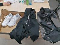 Zdjęcie przedstawia parę butów koloru białego, czarną bluzę, torbę sportowa koloru szaroczarnego.