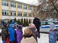 Grupa dzieci wraz z umundurowanym policjantem stojącym przed oznakowanym radiowozem