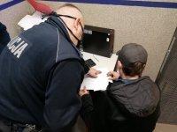 Umundurowany policjant wskazuje miejsce podpisu podejrzanemu.