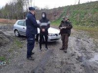 Umundurowany policjant i strażnik leśny w trakcie kontroli pojazdu.