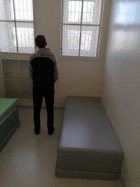 Zatrzymany mężczyzna, stojący tyłem w policyjnym areszcie.