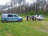 2 umundurowanych policjantów oraz 2 umundurowanych strażników leśnych, radiowóz oznakowany Poicji, pojazd oznakowany Straży Leśnej, na tle lasu.