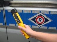 Urządzenie do badania zawartości alkoholu w wydychanym powietrzu , na tle radiowozu oznakowanego.