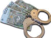 Kajdanki policyjne na tle 3 banknotów 100 złotowych.